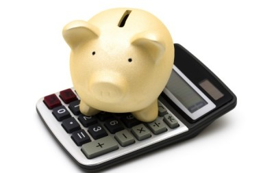 Piggy bank sitting on a calculator isolated on white